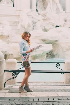 Mooie vrouw die een toeristische kaart kijkt dichtbij de fontein van trevi