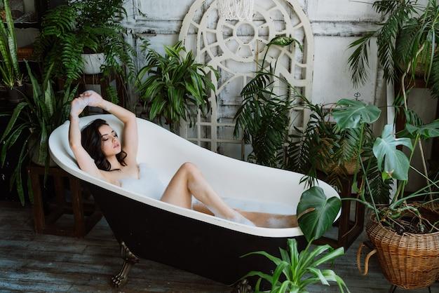 Mooie vrouw die een warm bad neemt in haar huis op het platteland