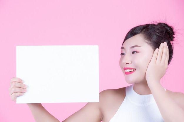 Mooie vrouw die een wit raadsblad op een roze achtergrond houdt.
