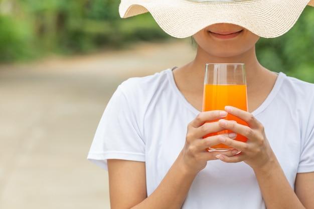 Mooie vrouw die een wit t-shirt draagt dat een glas jus d'orange houdt