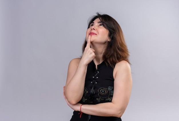 Mooie vrouw die een zwarte blouse draagt die thouhtfully omhoog kijkt