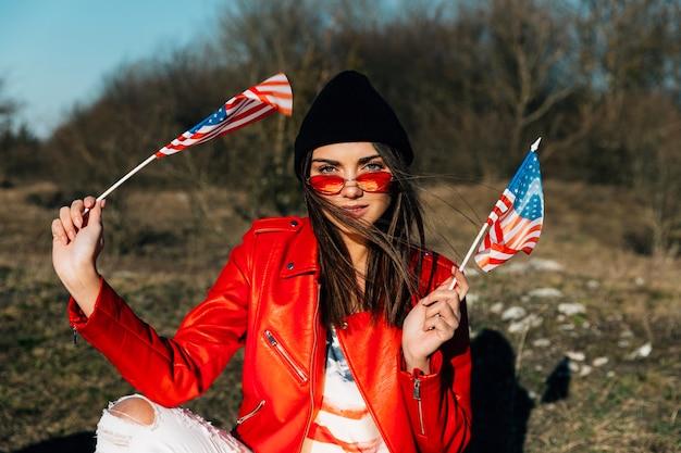 Mooie vrouw die en amerikaanse vlaggen stelt houdt