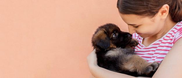 Mooie vrouw die en de ogen van de zwarte puppy houdt onderzoekt