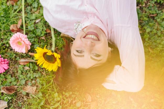 Mooie vrouw die en op gras glimlacht ligt