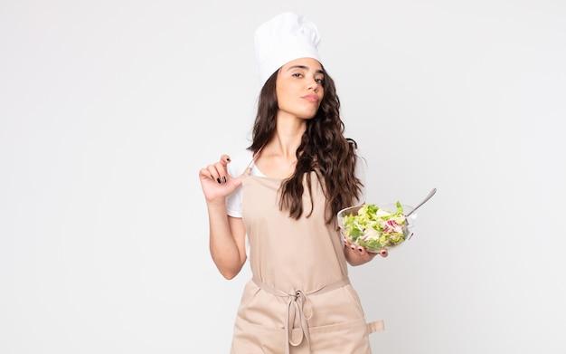 Mooie vrouw die er arrogant, succesvol, positief en trots uitziet, een schort draagt en een salade vasthoudt