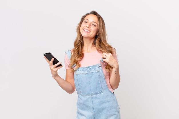 Mooie vrouw die er arrogant, succesvol, positief en trots uitziet en een smartphone vasthoudt