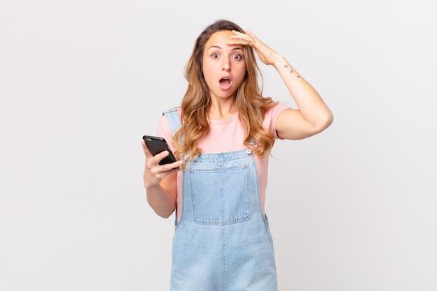 Mooie vrouw die er blij, verbaasd en verrast uitziet en een smartphone vasthoudt