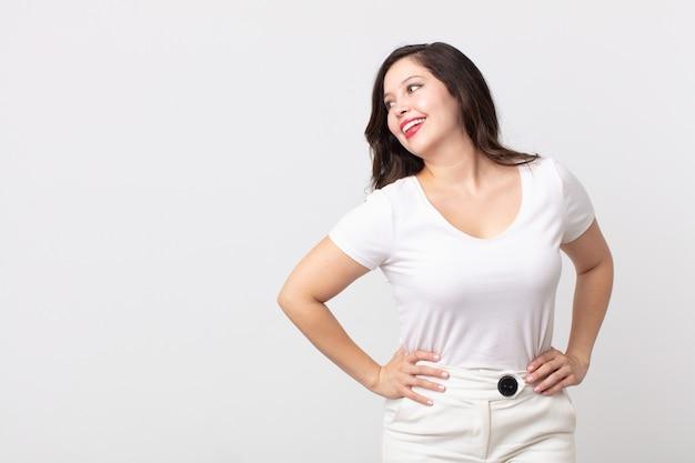 Mooie vrouw die er gelukkig, vrolijk en zelfverzekerd uitziet, trots lacht en opzij kijkt met beide handen op de heupen