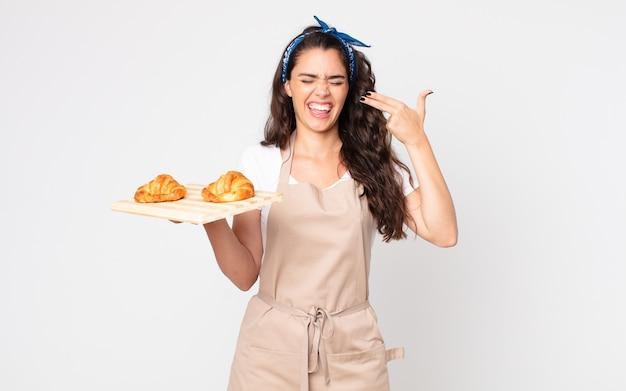 Mooie vrouw die er ongelukkig en gestrest uitziet, zelfmoordgebaar maakt een pistoolteken en houdt een dienblad met croissants