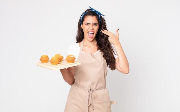 Mooie vrouw die er ongelukkig en gestrest uitziet, zelfmoordgebaar maakt een pistoolteken en houdt een dienblad met muffins