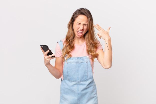 Mooie vrouw die er ongelukkig en gestrest uitziet, zelfmoordgebaar maakt een pistoolteken en houdt een smartphone vast