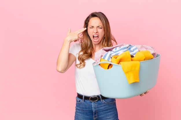 Mooie vrouw die er ongelukkig en gestrest uitziet, zelfmoordgebaar maakt een pistoolteken en wast kleren.