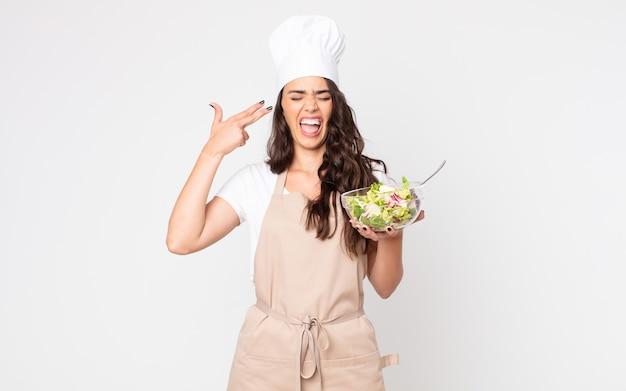 Mooie vrouw die er ongelukkig en gestrest uitziet, zelfmoordgebaar maakt een pistoolteken met een schort en een salade vast
