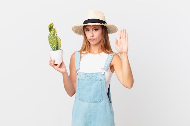 Mooie vrouw die er serieus uitziet met een open palm die een stopgebaar maakt en een decoratieve cactusplant vasthoudt