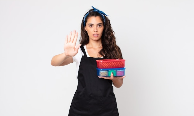 Mooie vrouw die er serieus uitziet met een open palm die een stopgebaar maakt en tupperwares met eten vasthoudt