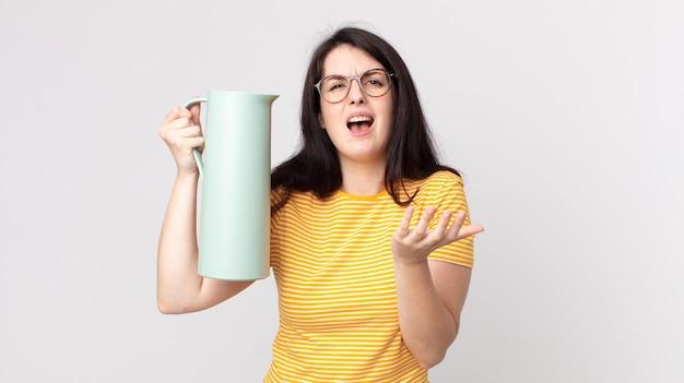 Mooie vrouw die er wanhopig, gefrustreerd en gestrest uitziet en een koffiethermoskan vasthoudt