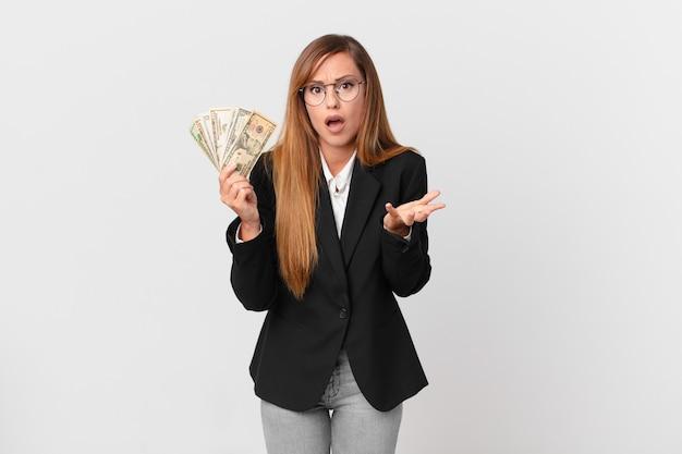 Mooie vrouw die er wanhopig, gefrustreerd en gestrest uitziet. zakelijk en dollars concept