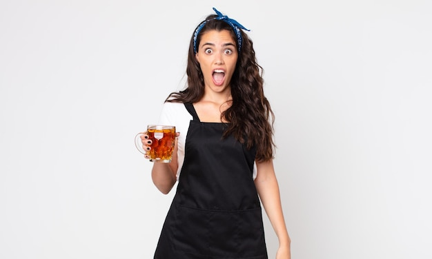 Mooie vrouw die erg geschokt of verrast kijkt en een pint bier vasthoudt