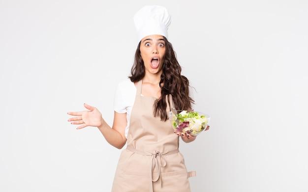 Mooie vrouw die erg geschokt of verrast kijkt terwijl ze een schort draagt en een salade vasthoudt