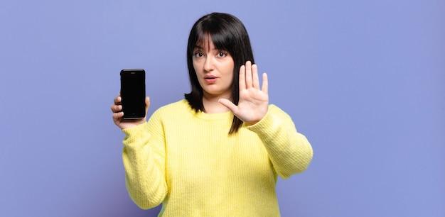 Mooie vrouw die ernstig, streng, ontevreden en boos kijkt die open palm toont die stopgebaar maakt
