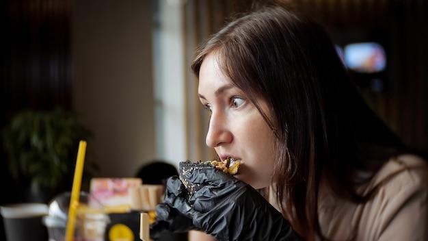 Mooie vrouw die fastfood-hamburger eet in café, zijaanzicht