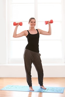 Mooie vrouw die fitnesstraining thuis doet