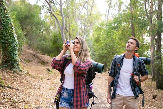 Mooie vrouw die foto van landschap met camera neemt en met vriend reist. kaukasische toeristen die samen wandelen. mannelijke backpacker die landschap bekijkt. toerisme, avontuur en zomervakantie concept