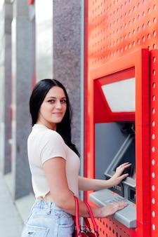 Mooie vrouw die geld uit de geldautomaat haalt.