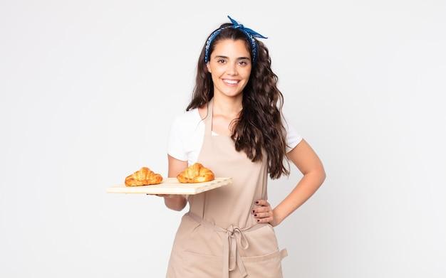 Mooie vrouw die gelukkig lacht met een hand op de heup en zelfverzekerd en een dienblad met croissants vasthoudt
