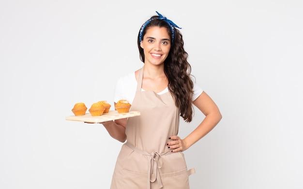 Mooie vrouw die gelukkig lacht met een hand op de heup en zelfverzekerd en een dienblad met muffins vasthoudt