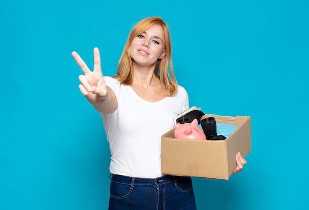 Mooie vrouw die gelukkig, zorgeloos en positief glimlacht en kijkt, met één hand overwinning of vrede gebaart