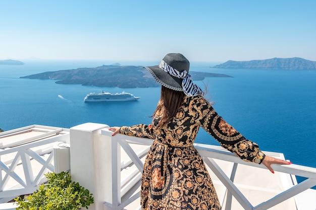 Mooie vrouw die geniet van het uitzicht op het eiland santorini en de caldera in de egeïsche zee