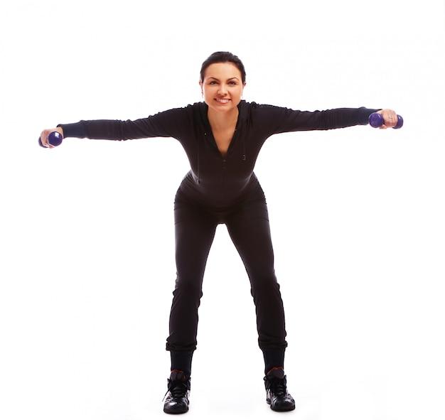 Mooie vrouw die geschiktheidsoefeningen met gewichten doet