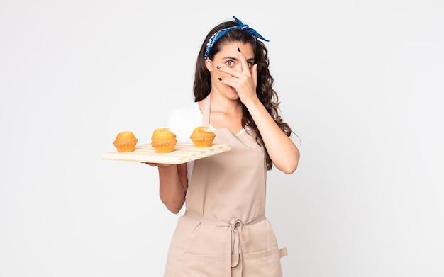 Mooie vrouw die geschokt, bang of doodsbang kijkt, haar gezicht bedekt met de hand en een dienblad met muffins vasthoudt