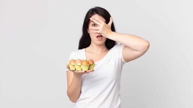 Mooie vrouw die geschokt, bang of doodsbang kijkt, haar gezicht bedekt met de hand en een eierdoos vasthoudt