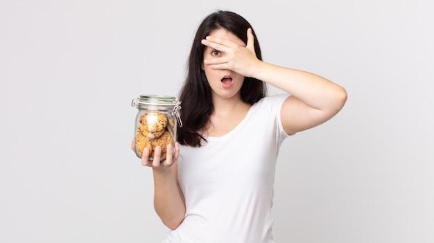 Mooie vrouw die geschokt, bang of doodsbang kijkt, haar gezicht bedekt met de hand en een glazen fles met koekjes vasthoudt
