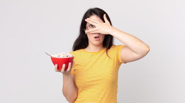Mooie vrouw die geschokt, bang of doodsbang kijkt, haar gezicht bedekt met de hand en een ontbijtkom vasthoudt
