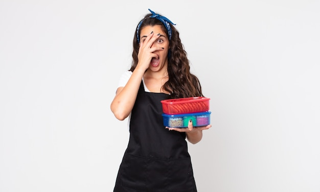 Mooie vrouw die geschokt, bang of doodsbang kijkt, haar gezicht bedekt met hand en tupperware vasthoudt met eten