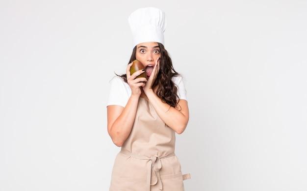Mooie vrouw die geschokt en bang is, een schort draagt en een mango vasthoudt