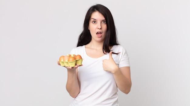 Mooie vrouw die geschokt en verrast kijkt met wijd open mond, wijzend naar zichzelf en een eierdoos vasthoudend