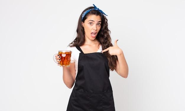 Mooie vrouw die geschokt en verrast kijkt met wijd open mond, wijzend naar zichzelf en een pint bier vasthoudend