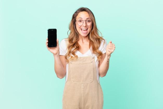Mooie vrouw die geschokt is, lacht en succes viert en een smartphone vasthoudt