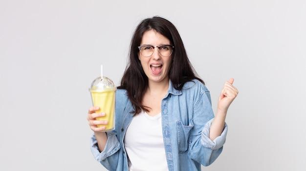 Mooie vrouw die geschokt is, lacht en succes viert en een vanillemilkshake vasthoudt