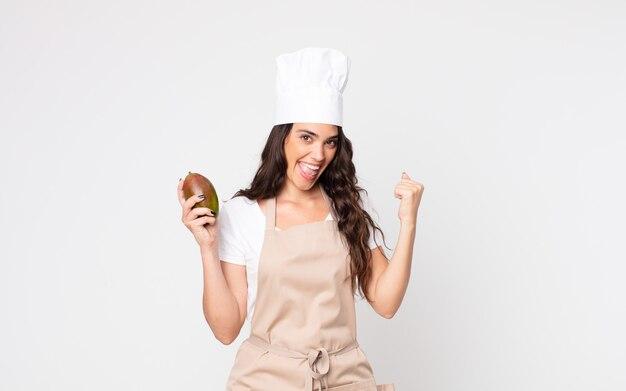 Mooie vrouw die geschokt is, lacht en succes viert met een schort en een mango in haar hand