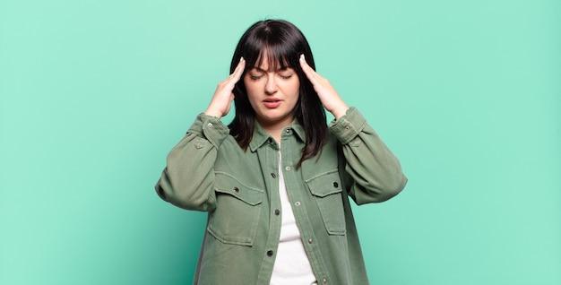 Mooie vrouw die gestrest en gefrustreerd kijkt, onder druk werkt met hoofdpijn en last heeft van problemen