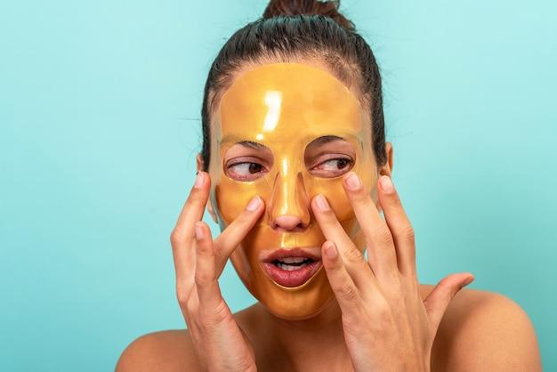 Mooie vrouw die gezichtsbehandeling van het de huidverzorgingsmasker van de collageengel gebruikt