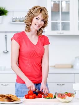 Mooie vrouw die gezond voedsel in de keuken kookt