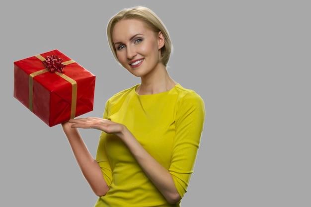 Mooie vrouw die giftdoos op grijze achtergrond voorstelt. aantrekkelijke vrouw die huidige doos toont. krijg uw vakantiekorting.