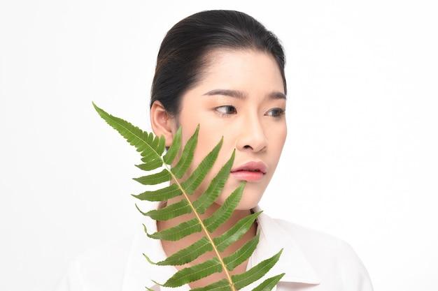 Mooie vrouw die groene installatie houdt.