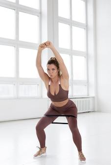 Mooie vrouw die gymnastiekoefening doet